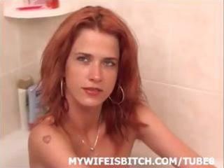 slim redhead wife is in the tub posing and