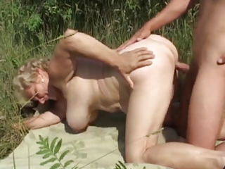 german granny outdoor with youthful lad by troc